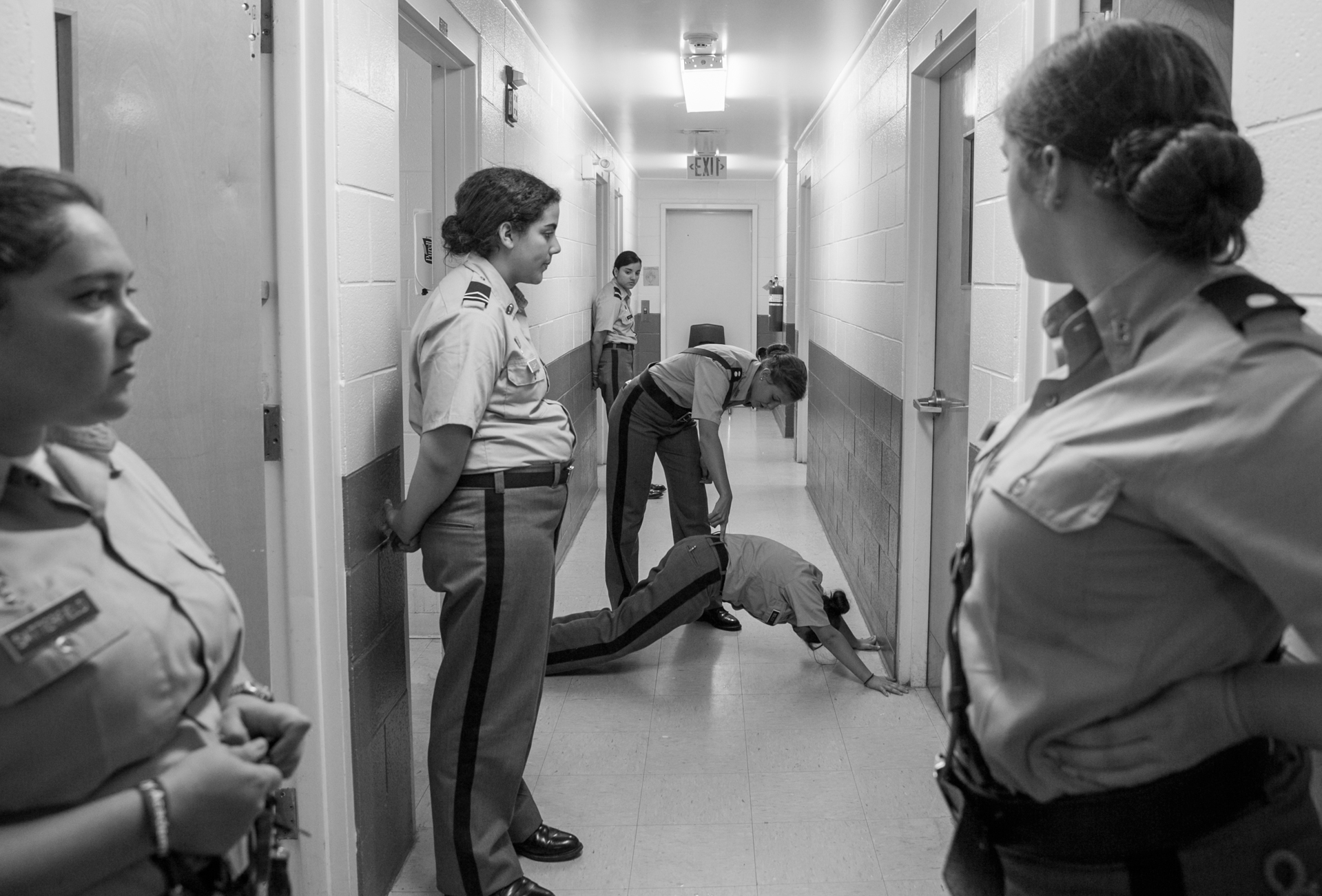 Capt. Whitehead makes sure that a younger cadet does proper pushups while other cadets in the dorm wait for room inspection. The cadet was ordered to do pushups because her room was not properly cleaned prior to room inspection.