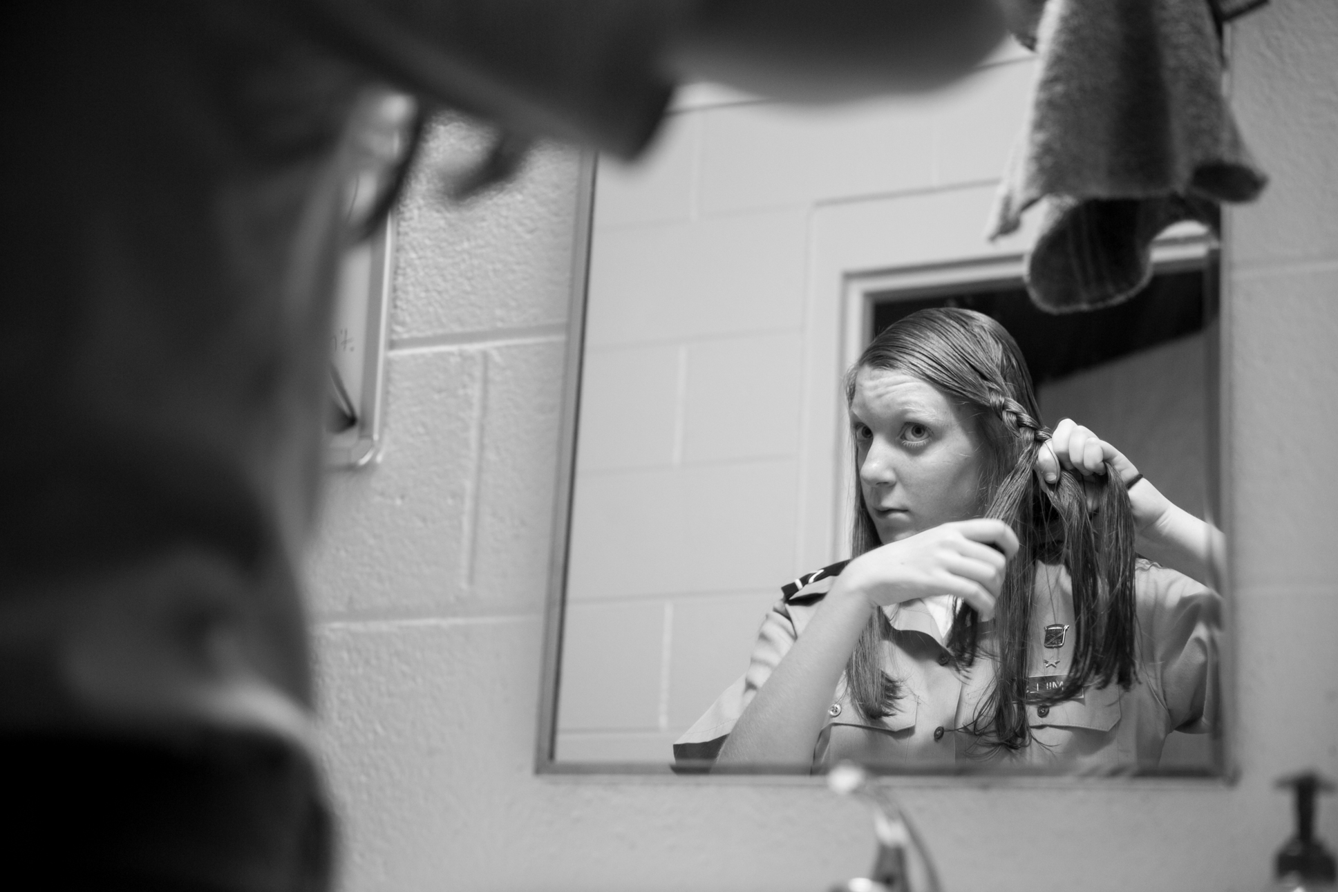 PVT Mills braids her hair before morning formation. The male cadets are required to keep their hair cut short and neat. While the girls are not required to cut their hair, they must keep it structured and pulled back at all times except while in the dorms.